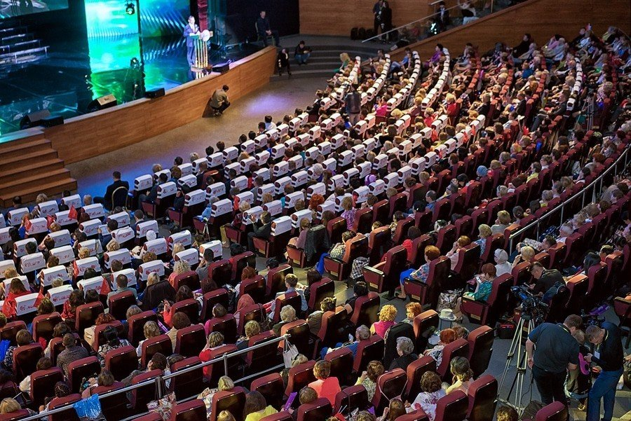 Photo of a full auditorium at a conference.
