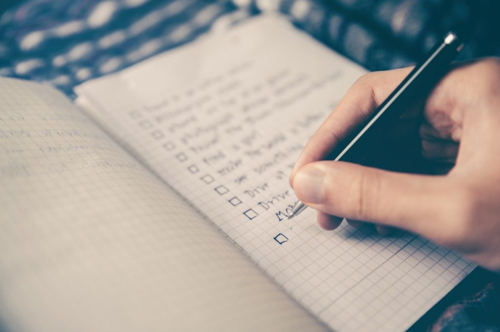 writing down a checklist in a notebook